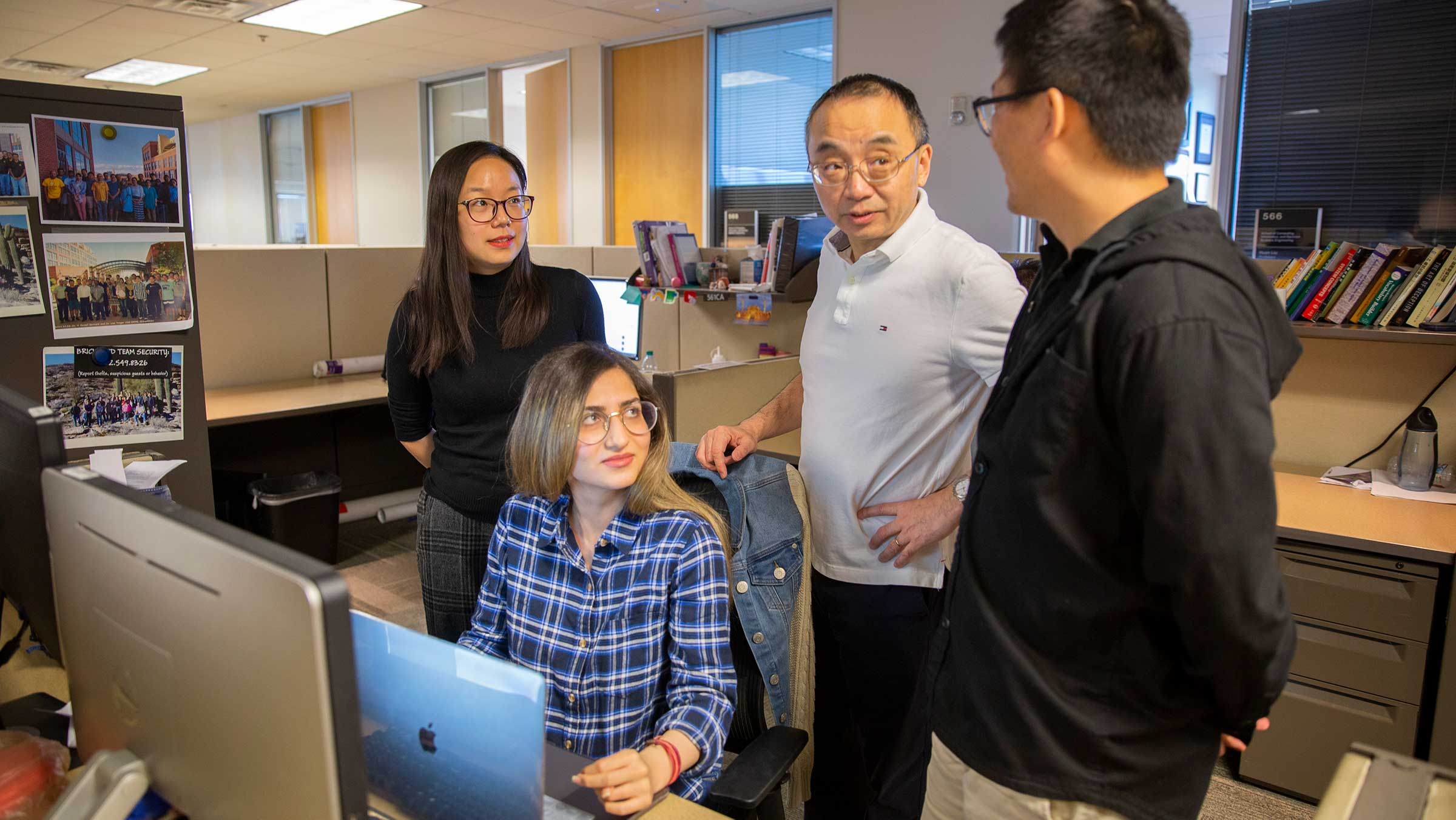 A faculty memeber stands at a desk with three students, discussing data on the computer screen