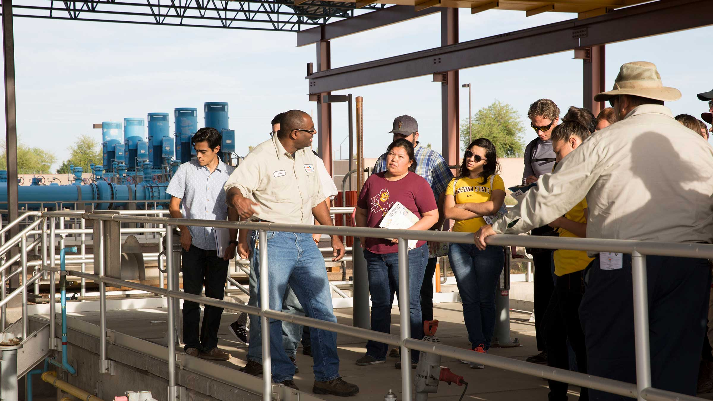 A group of students stands outdoors with their instructor learning at the water treatment plant