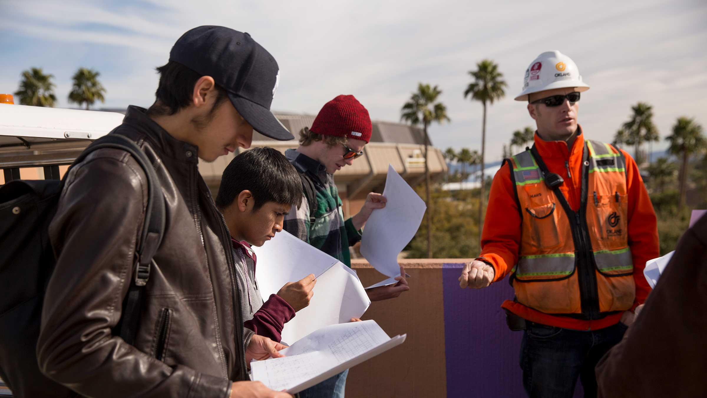 A group of students stand with their professor in class at a construction site.