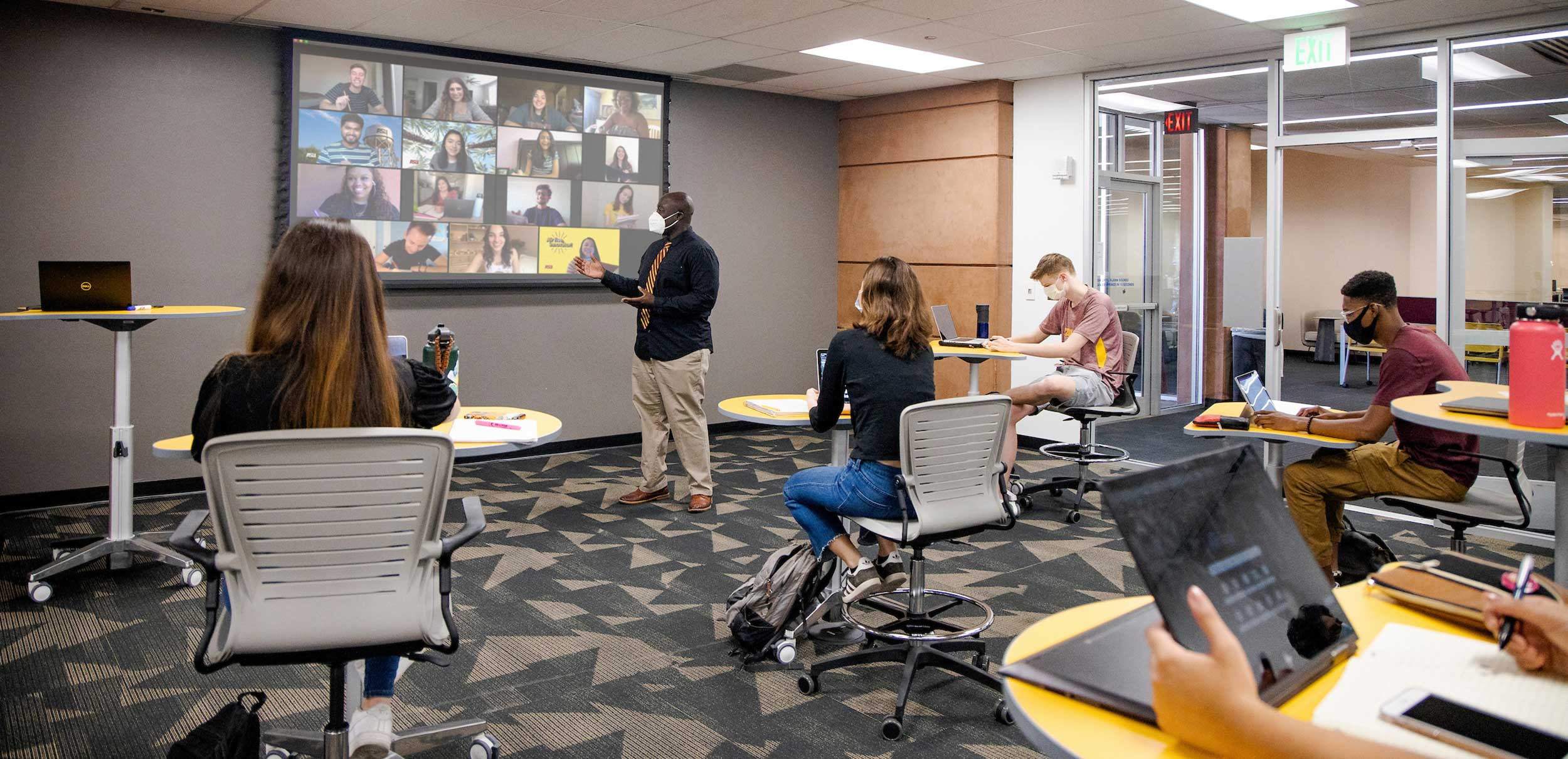 A teacher stands at the front of a class, where on screen we see the faces of remote participants and in-person participants physically in the classroom