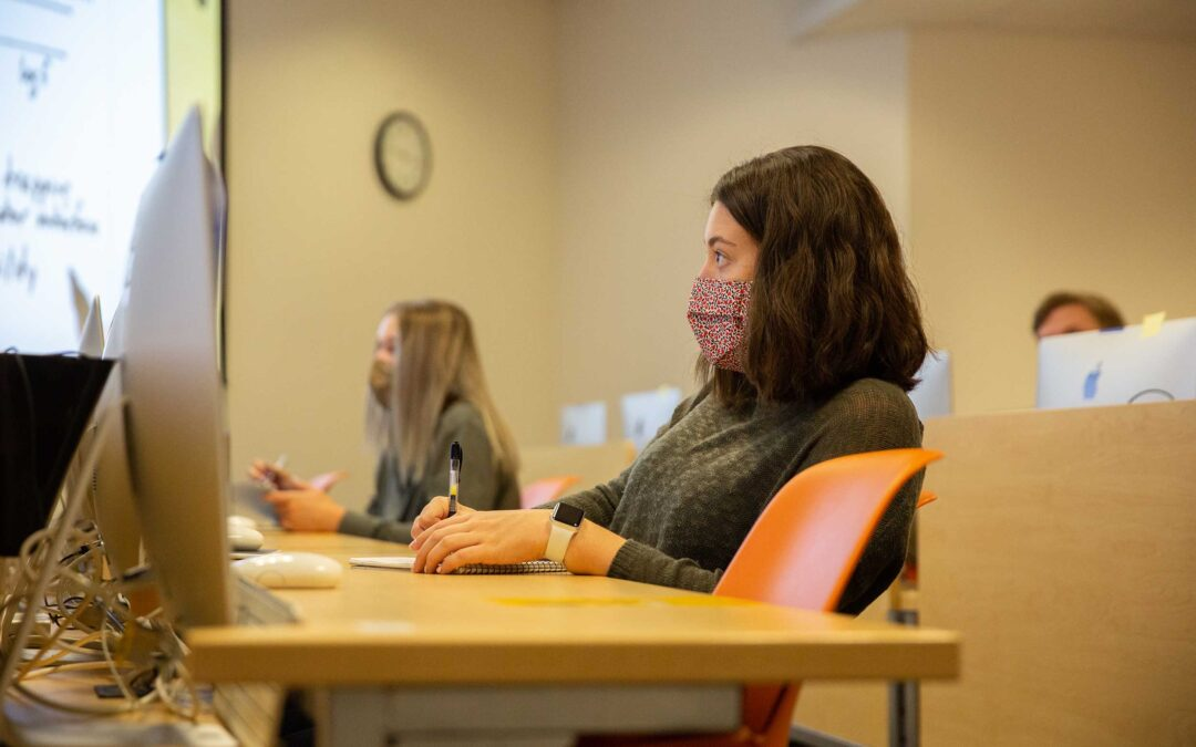 Two women sit socially distanced in a classroom while attending a lecture by DSAE faculty member David Allee